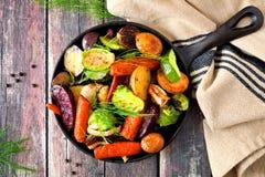 Koekepan van geroosterde groenten, luchtscène op rustiek hout stock fotografie