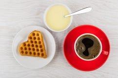 Koekje op schotel, koffie, condens en lepel op lijst stock afbeelding