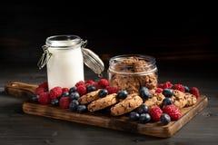 Koekjes, bessen en melk op houten bodem, zijaanzicht royalty-vrije stock afbeeldingen