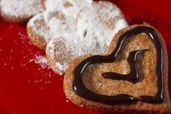 Koekjes in de vorm van harten met suikerglazuursuiker en chocolade cre Stock Foto's