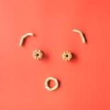 Koekjes gestalte gegeven gezicht De cakes van bloemkoekjes op roze achtergrond Vlak leg stock foto