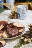 Koekjes, kaarsen en denneappels op vakantieservet Stock Foto