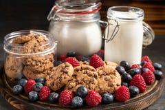 Koekjes, melk, bloemontvangers en bosvruchten die op rond gemaakt houten schotelclose-up worden geplaatst stock afbeelding