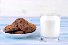 Koekjes met chocolade op een plaat en melk in een glas op een blauwe houten achtergrond baksel yummy stock afbeelding
