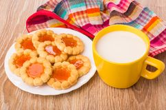 Koekjes met jam in witte plaat, melk en geruit servet royalty-vrije stock afbeeldingen