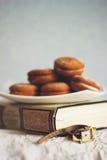Koekjes op een witte plaat op een oud boek Stock Foto's
