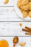 Koekjes, oranje jam, pijpjes kaneel op witte houten achtergrond Stock Afbeelding