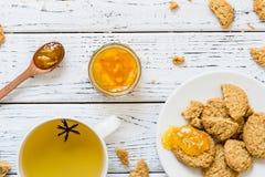 Koekjes, oranje jam, thee met anijsplant op witte houten achtergrond Royalty-vrije Stock Afbeeldingen
