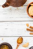 Koekjes, oranje jam, thee, pijpjes kaneel op witte houten achtergrond Stock Afbeelding