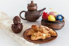 Koekjes, zoete chocolade, kip, ketel met thee, en geschilderde eieren in de Pasen-vakantie stock foto's