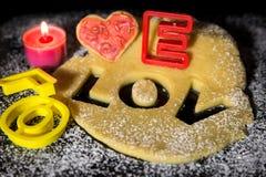 Koekjesdeeg en koekjessnijder op een zwarte steen met suikerglazuursuiker Stock Fotografie