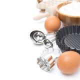 Koekjessnijders, metende lepels, eieren en bloem voor baksel Royalty-vrije Stock Foto's