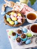 Koekt de zoete kop van Pasen treets in kleurrijke eishells op blauw Royalty-vrije Stock Fotografie