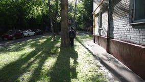Koel het gemengde jongen lopen buiten zijn huis na school stock video