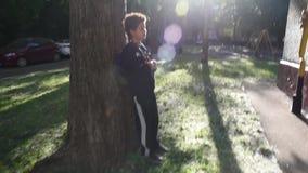 Koel het gemengde jongen lopen buiten zijn huis na school stock videobeelden
