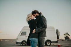 Koel jong paar die elkaar in openlucht kussen terwijl zij, tijdens een einde van de wegreis, met hun bestelwagen op de achtergron royalty-vrije stock foto