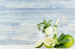 Koel transparante de zomerlimonade in glas met stro en ingrediënten - groene komkommer, kalk, munt op retro blauwe houten raad Stock Afbeelding