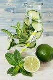 Koel transparante de zomerlimonade in glas met stro, fles en ingrediënten - groene komkommer, kalk, munt op retro blauwe houten r Royalty-vrije Stock Foto