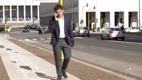 Koele bedrijfsmens in stad die op straat met smartphone spreken stock videobeelden