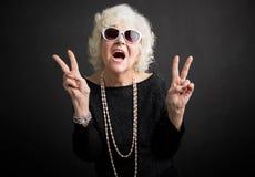 Koele grootmoeder die vredesteken tonen royalty-vrije stock fotografie