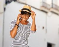 Koele jonge Afrikaanse Amerikaanse vrouw die aan celtelefoon luisteren royalty-vrije stock afbeeldingen