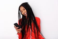 Koele jonge Afrikaanse Amerikaanse vrouw het luisteren muziek met hoofdtelefoon en mobiele telefoon royalty-vrije stock foto's