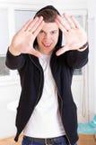 Koele jonge kerel in jasje die met een kap zijn gezicht met handen ontwerpen Royalty-vrije Stock Foto's