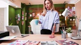 Koele jonge media schepper die haar laatste ideeën op haar bureau tonen stock video
