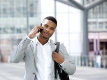 Koele jonge mens met zak die op mobiele telefoon spreken Stock Foto