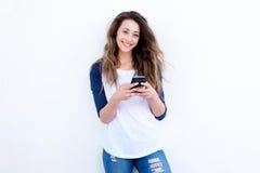 Koele jonge vrouw die met mobil telefoon tegen witte achtergrond glimlachen royalty-vrije stock afbeelding