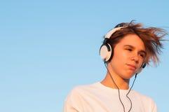 Koele Jongen die aan Muziek luisteren Stock Fotografie