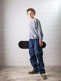 Koele Jongen en zijn skateboard Stock Foto's