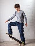 Koele Jongen op zijn skateboard Stock Foto's