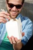 Koele kerel die meeneemvoedsel met eetstokjes eten stock foto's