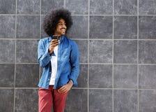 Koele kerel die met afro cellphone gebruiken Stock Fotografie