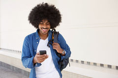 Koele kerel die met mobiele telefoon en zak lopen Stock Foto's