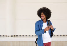 Koele kerel die met zak en cellphone glimlachen Stock Foto