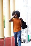 Koele kerel die op de dragende zak van de celtelefoon in stad spreken Royalty-vrije Stock Fotografie