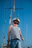 Koele knap weinig jong geitjekapitein aan boord van luxejacht stock foto