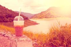 Koele koffie in plastic koppen, met achtergrondmeningen als reservoirs stock afbeeldingen