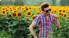 Koele mannelijk-landbouwer het dansen pret op zonnebloemengebied, tevreden en positief op zonsondergang De landbouwconcept stock footage
