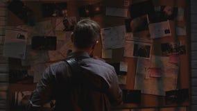 Koele mannelijke detective die onderzoeksraad bekijken, die naar oplossing zoeken stock videobeelden