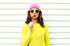 Koele meisje van de portretmanier het vrij met lolly die rode lippen in kleurrijke kleren over witte achtergrond blazen die een r Stock Foto