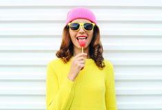 Koele meisje van de portretmanier het vrij met lolly in kleurrijke kleren over witte achtergrond die een roze hoeden gele zonnebr Stock Fotografie