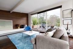 Koele midden van de eeuw moderne zitkamer met vooruitzichten voor terras stock foto