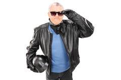 Koele rijpe motorrijder die een helm houden Stock Foto's