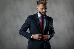 Koele sexy jonge zakenman die zijn kostuum en blikken neer dichtknopen stock foto
