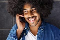 Koele vrolijke kerel die celtelefoon met behulp van Stock Foto's