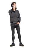 Koele zekere ernstige hipster die grijs jasje en militaire laarzen dragen die op cellphone spreken die weg eruit zien Stock Afbeelding