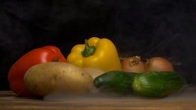 Koelen de de de de verse groenten Bulgaarse peper, komkommers, aardappels en uien op een zwarte achtergrond van de groentenslagen stock videobeelden